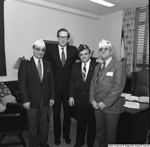 "[""Three unidentified members of the American Legion pose for a photograph with Senator John D. (Jay) Rockefeller in his Washington office.""]%"