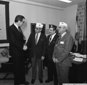 "[""Senator John D. (Jay) Rockefeller shakes the hand of an unidentified member of the American Legion in his Washington, D.C. office.""]%"