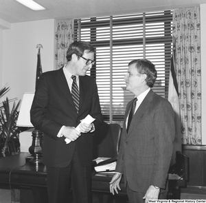 "[""Senator John D. (Jay) Rockefeller holds a rolled up piece of paper as he speaks with FEMA Assistant Director Sam Speck in his Washington office.""]%"