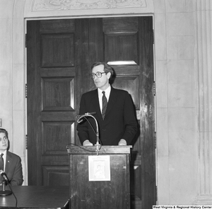 "[""Senator John D. (Jay) Rockefeller speaks at an event and stands behind a podium with a \""babies don't come with directions\"" poster attached to it.""]%"