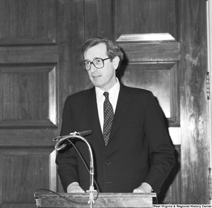 "[""Senator John D. (Jay) Rockefeller stands behind a podium and speaks at an unknown event.""]%"