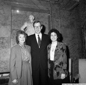 "[""Senator John D. (Jay) Rockefeller stands between two unidentified women in front of a statue at a Senate building.""]%"