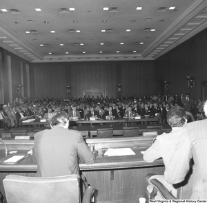 "[""This photograph shows the audience at a committee hearing at the Senate. This appears to be a Veterans Affairs committee hearing and there are a large number of American Legion members in the audience.""]%"