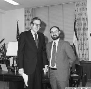 "[""Senator John D. (Jay) Rockefeller stands in front of his desk and poses for a photograph with an unidentified individual.""]%"