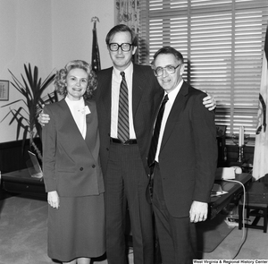 "[""Senator John D. (Jay) Rockefeller poses for a photograph with and embraces two unidentified guests in front of the desk in his Washington office. The woman in the photograph has a name badge on that appears to say NASA on it.""]%"