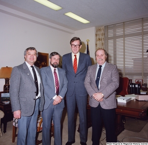 "[""Senator John D. (Jay) Rockefeller stands for this color photograph in front of the desk in his office with three representatives from the West Virginia Homebuilders Association.""]%"