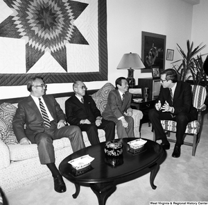 "[""Senator john D. (Jay) Rockefeller sits in a chair and speaks with the president of Nisshin and two others in his Washington office.""]%"