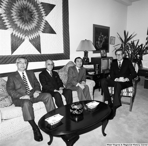 "[""Senator John D. (Jay) Rockefeller sits in a chair in his office with a group of unidentified individuals.""]%"