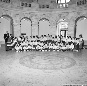 "[""Senator John D. (Jay) Rockefeller and Congressman Nick Rahall hold an american flag and pose for a photograph with a large group of young students in a rotunda.""]%"