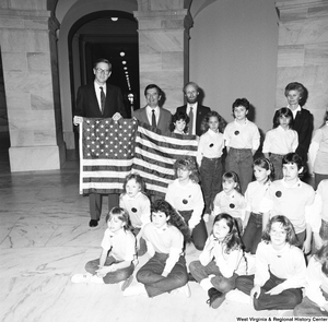 "[""This photograph shows a close-up of Senator John D. (Jay) Rockefeller, Congressman Nick Rahall, and a young student holding an American flag during the student group's visit to the Capital.""]%"