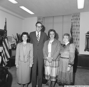 "[""Senator John D. (Jay) Rockefeller stands for a photograph in front of his desk with three unidentified women.""]%"