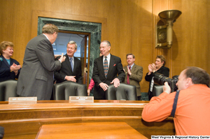 "[""A group of Senators greet Senator Max Baucus as he enters the Senate Finance Committee hearing room.""]%"