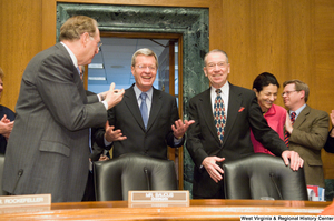 "[""Photograph of Senator Max Baucus being greeted by Senators John D. (Jay) Rockefeller and Charles Grassley as he enters the Finance Committee hearing room.""]%"