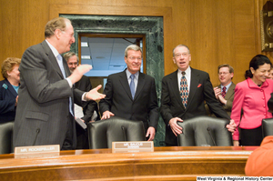 "[""Senator John D. (Jay) Rockefeller claps for new Senate Finance Committee chairman, Senator Max Baucus.""]%"