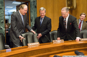 "[""Senator John D. (Jay) Rockefeller helps pull out the chair for Senator Max Baucus at the beginning of a Senate Finance Committee hearing.""]%"