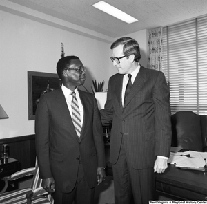 "[""Senator John D. (Jay) Rockefeller stands in front of the desk in his office with FEMA Director Julius Beckton.""]%"