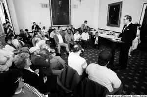 "[""Senator John D. (Jay) Rockefeller speaks about black lung disease in West Virginia with a group in a room in the Senate.""]%"