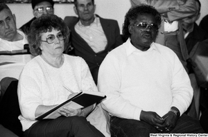 "[""A woman sits beside an unidentified man and takes notes during a speech by Senator John D. (Jay) Rockefeller.""]%"