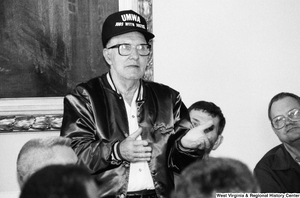 "[""A man wearing a UMWA hat stands to ask Senator John D. (Jay) Rockefeller a question.""]%"
