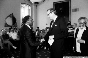"[""Senator John D. (Jay) Rockefeller shakes hands with an unidentified man.""]%"
