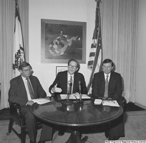 "[""Senator John D. (Jay) Rockefeller sits with two representatives from Consumers United for Rail Equity and the National Coal Association during a press event to announce West Virginia coal savings.""]%"
