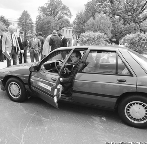 "[""Senator John D. (Jay) Rockefeller exits a General Motors gasoline/methanol car outside the Senate.""]%"