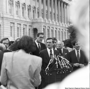 "[""Senator John D. (Jay) Rockefeller standing outside the Senate while another man speaks.""]%"