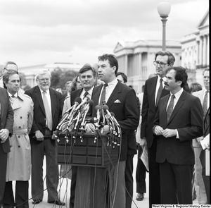 "[""A man speaks at a press event outside the Senate.""]%"