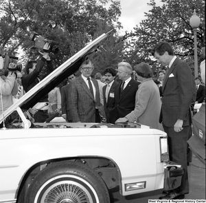 "[""Senator Robert C. Byrd looks at the motor of a car at an alternative motor fuels event outside the Senate building.""]%"