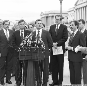 "[""Senator John D. (Jay) Rockefeller stands behind a man speaking at an alternative motor fuels event outside the Senate.""]%"