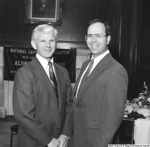 "[""West Virginia University President Neil S. Bucklew stands for a photograph with an unidentified individual at an event hosted by the National Capitol Chapter of the West Virginia University Alumni Foundation.""]%"