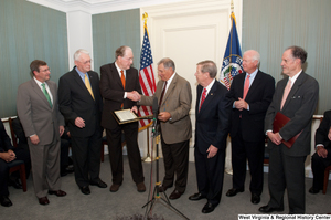 "[""A group of Senators gather together to celebrate a piece of legislation.""]%"