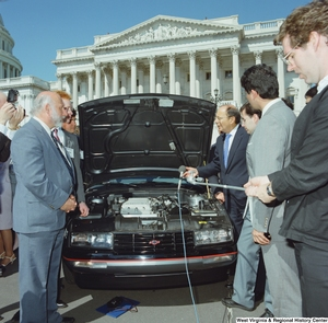 "[""Members of West Virginia University's clean energy vehicle team show off their car's engine to a group of people outside the Senate.""]%"