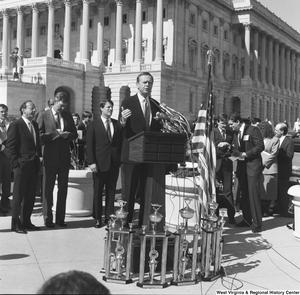 "[""An unidentified man speaks to the crowd at a clean vehicle event outside the Senate.""]%"