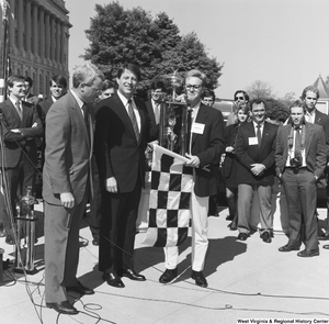 "[""Senator Al Gore stands with a trophy at a clean vehicle event outside the Senate.""]%"