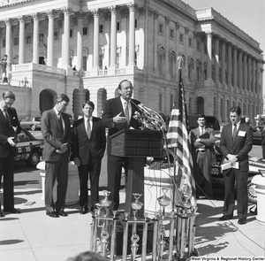 "[""Senator John D. (Jay) Rockefeller stands behind as a man speaks at a clean vehicle competition outside the Senate.""]%"