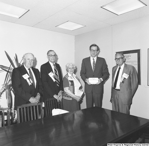 "[""Senator John D. (Jay) Rockefeller stands for a photograph with four representatives of the American Association of Retired Persons. The Senator holds a box that reads \""First Aid for Medicare and Medicaid\"".""]%"