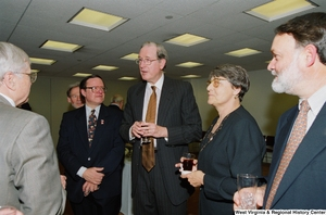 "[""Senator John D. (Jay) Rockefeller speaks with unidentified individuals at a recognition ceremony hosted by the Federation of American Women's Clubs Overseas.""]%"