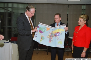 "[""Senator John D. (Jay) Rockefeller holds a map titled \""A Salute to 4.1* Million Americans Living Abroad\"" as he attends a recognition ceremony hosted by the Federation of American Women's Clubs Overseas.""]%"