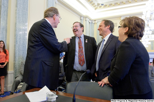 "[""Senator John D. (Jay) Rockefeller and tv personality Mike Rowe laugh before a Commerce Committee hearing.""]%"