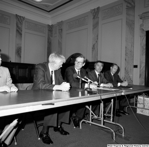 "[""Senator John D. (Jay) Rockefeller sits behind a table at a press event.""]%"