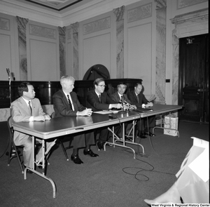 "[""Senator John D. (Jay) Rockefeller sits behind a table at a press event in the Senate.""]%"