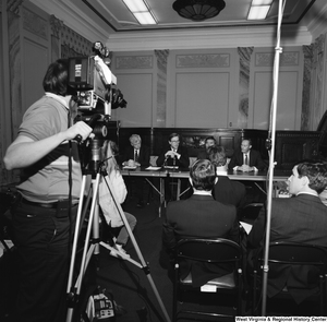 "[""A film crew captures a press event where Senator John D. (Jay) Rockefeller and several other men speak.""]%"