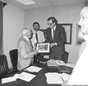 "[""Senator John D. (Jay) Rockefeller holds a photograph of people working on a railroad with an unidentified man.""]%"