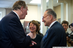 "[""Senators John D. (Jay) Rockefeller, Charles Schumer, and Amy Klobuchar laugh with one another after a press event for the Commerce Committee hearing.""]%"