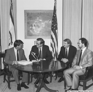 "[""Senator John D. (Jay) Rockefeller facilitates a business meeting between three representatives of steel companies.""]%"