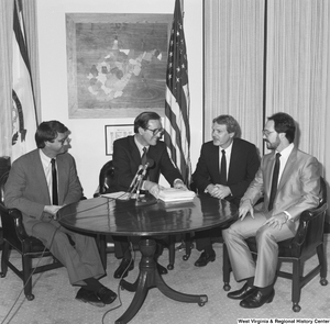 "[""Senator John D. (Jay) Rockefeller finishes a business meeting in his office with three steel industry representatives.""]%"