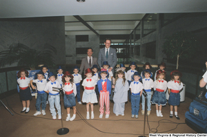 "[""Senator John D. (Jay) Rockefeller and Congressman Nick Rahall stand behind a group of kindergartners from Wayne County West Virginia who are dressed in patriotic costumes and appear to be ready to sing a song.""]%"