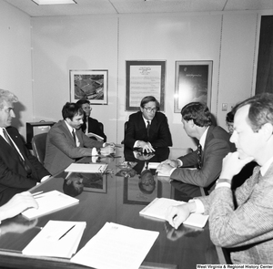 "[""Senator John D. (Jay) Rockefeller and Congressman Bob Wise sit at a conference table with several unidentified individuals.""]%"