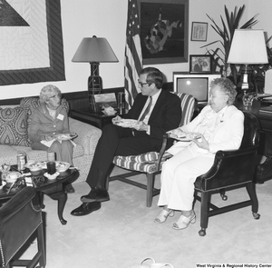 "[""Senator John D. (Jay) Rockefeller shares a meal with two unidentified women in his Washington office.""]%"